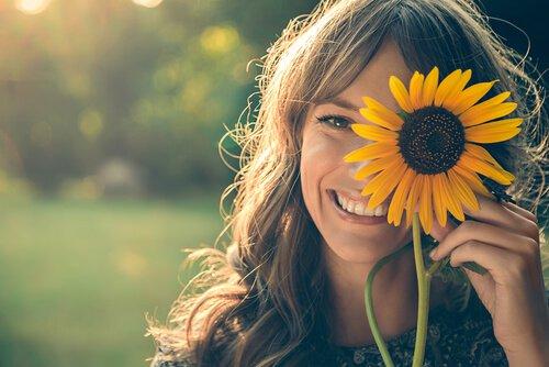 Chica-sonriendo-con-un-girasol-en-la-cara
